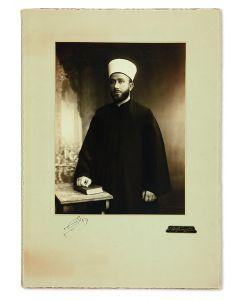 (Grand Mufti of Jerusalem, 1897-1974). Three-quarter length, silver-print photograph by C. Raad of Jerusalem, with Husseini autograph signature below.