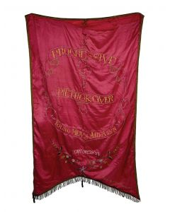 """Large, two sided, hand embroidered silk banner. Text in Yiddish and English surrounded by flowers. """"Made by Garechtman's."""" Tears in two spots on the edge (unaffecting signage). 30 x 52 inches (76 x.133 cm)."""